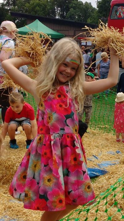 Child throwing hay at Playday.