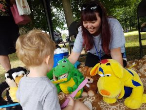 Lady at Playday teaching child how to brush teeth using teddies.